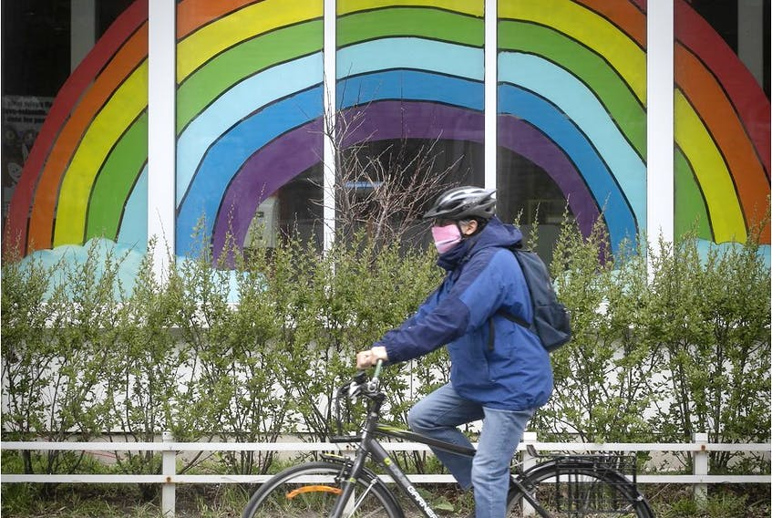 A cyclist wearing a mask rolls by a rainbow painted on a window on Sherbrooke St. on Tuesday, May 5, 2020.