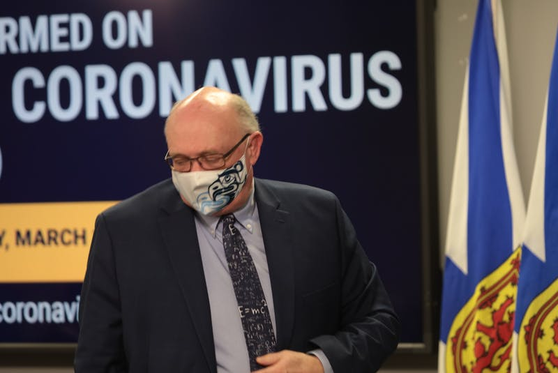 Dr. Robert Strang, Nova Scotia's chief medical officer of health, dons his mask at the conclusion of a COVID-19 update in March. The mask mandate has been expanded to outdoor areas of restaurants and bars as well as farm markets and festivals. -  Eric Wynne