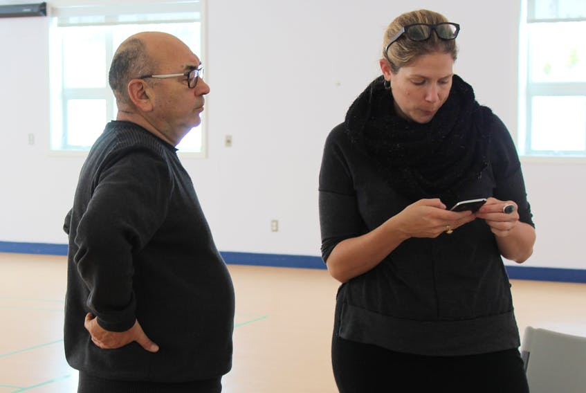 Indigenous and Northern Affairs Canada special representative Jim Igloliorte chats with a staffer during sessions of the residential schools healing and commemoration tour in Postville Feb. 26.