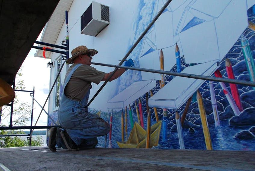 """Craig Goudie works on the 2017 mural titled """"The Two R's"""" painted on the town's library."""