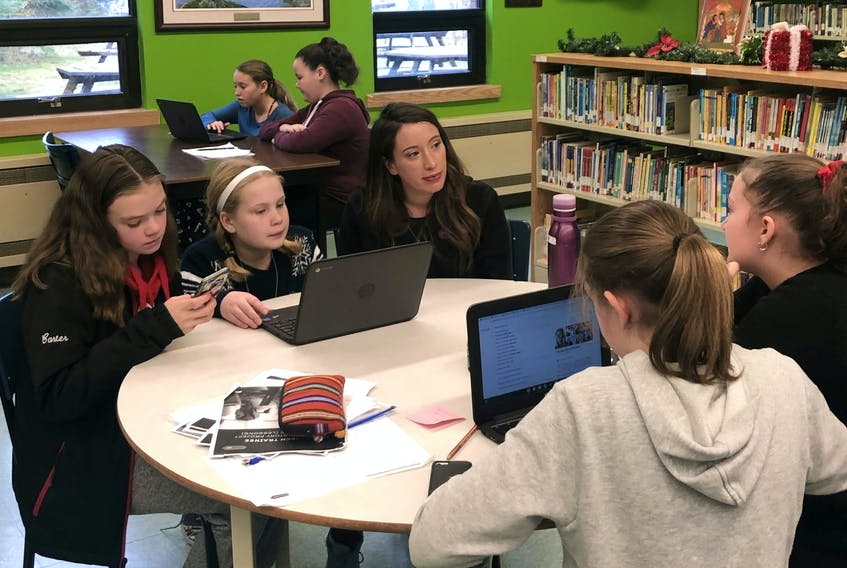 Hackaton founder Lucy Ho with some of the young women from Amalgamated Academy during the Hackathon on Dec. 10.