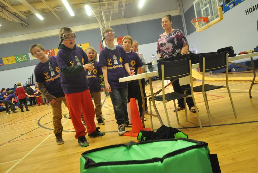A little impairment gave Grade 5 students an idea of how difficult it can be to do some of the easiest tasks, like tossing coins into a container. The impairment goggles worn by participants imitate the visual effects of alcohol.   Christopher Gooding/Amherst News