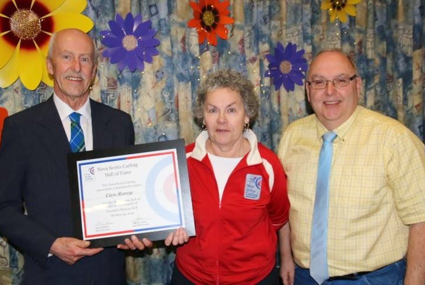 Nova Scotia Curling Association president Harry Daemen (left) presents a Hall of Fame award to Chris Manuge of the Amherst Curling Club while fellow Amherst curler Kim DeLong looks on.