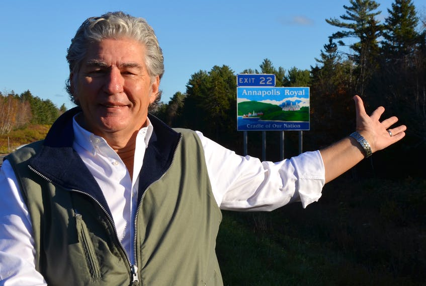 Annapolis Royal Mayor Bill MacDonald gestures towards a new Highway 101 sign that points to Annapolis Royal at Exit 22. The new sign proclaims the town as the 'Cradle of Our Nation.'