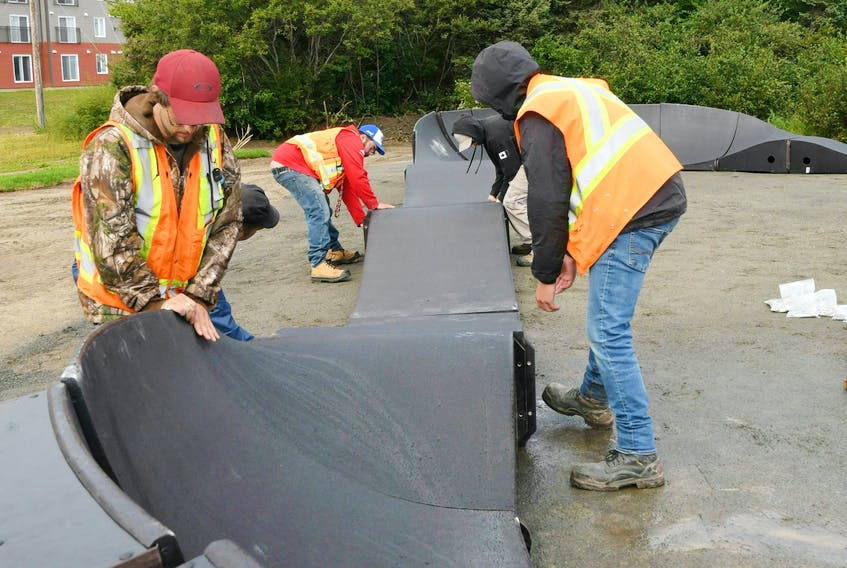 Workers from Labrador City recreation department assist Graham Cooke of Canadian Ramp Company with the assembly of the pump track.