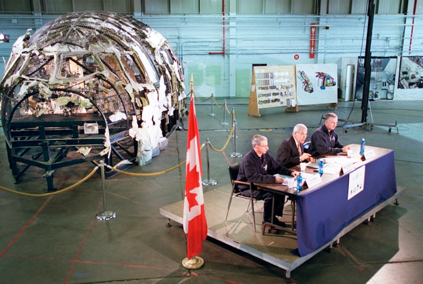 Transportation Safety Board Investigator-in-Charge Vic Gerden (L), Chairman Benoit Bouchard and Transportation Safety Board Senior Investigator Andre Turenne (r), give their recommendations following their investigations of the Swissair crash, in Hangar A at Canadian Forces Base Shearwater in March 2003. The very partially reconstructed cockpit area of the doomed jet, sits in the background.