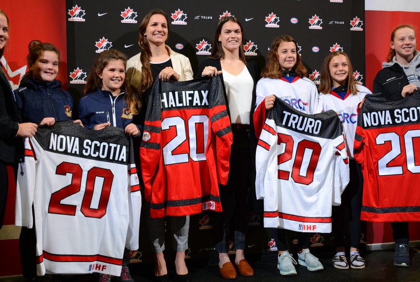 Jill Saulnier and Blayre Turnbull, members of the Canadian women's hockey team, are surrounded by minor hockey players from the Halifax area at the Scotiabank Centre in Halifax for the announcement Tuesday morning that the 2020 IIHF women's world championship will be co-hosted by Halifax and Truro. - Francis Campbell