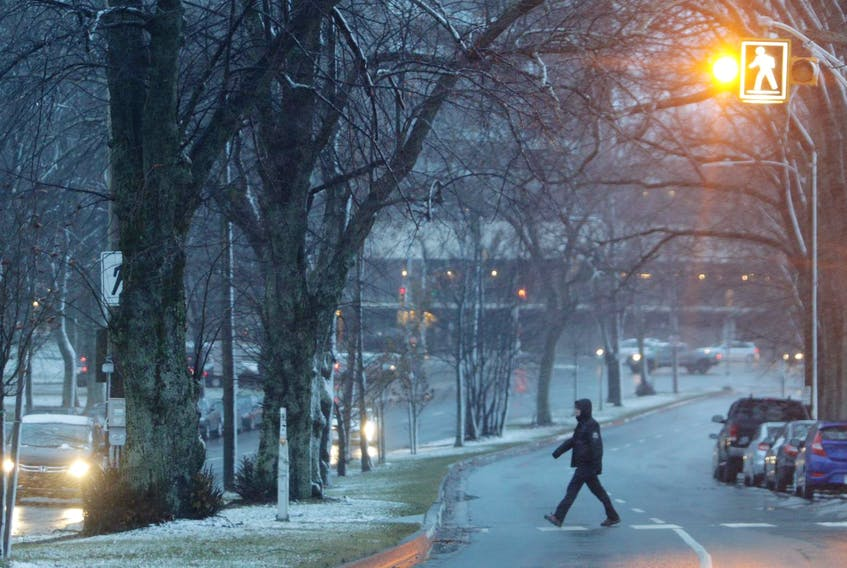 A pedestrian walks across a crosswalk on Cogswell Street in Halifax on Thursday morning. Nova Scotia is in the grips of another late fall storm. Halifax hasn't faired too badly as snow was turning to rain in the early morning, but more northern areas of the province are seeing mostly snow. - Eric Wynne