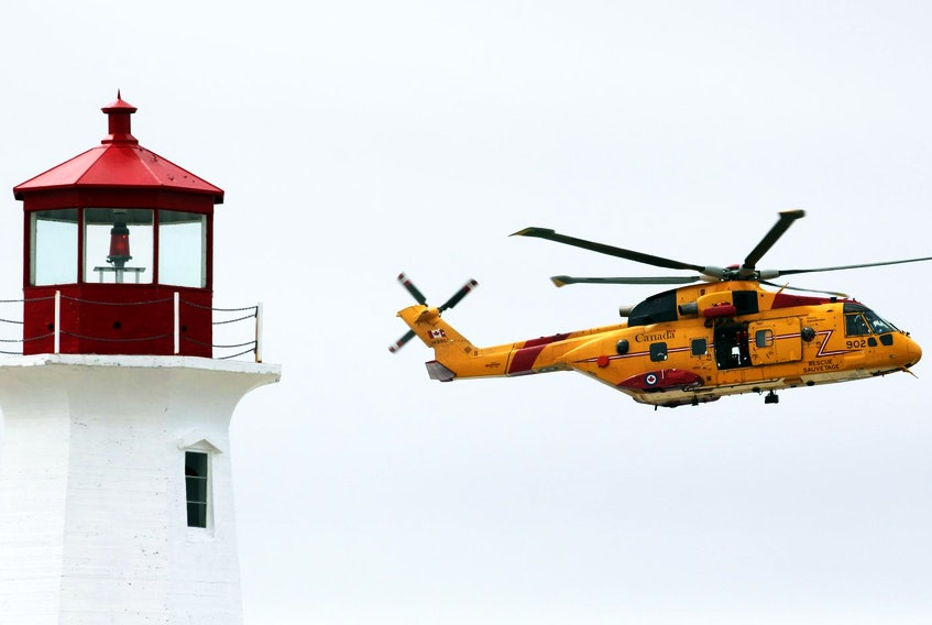 A coast guard Cormorant helicopter passes by the Peggys Cove lighthouse in 2015.