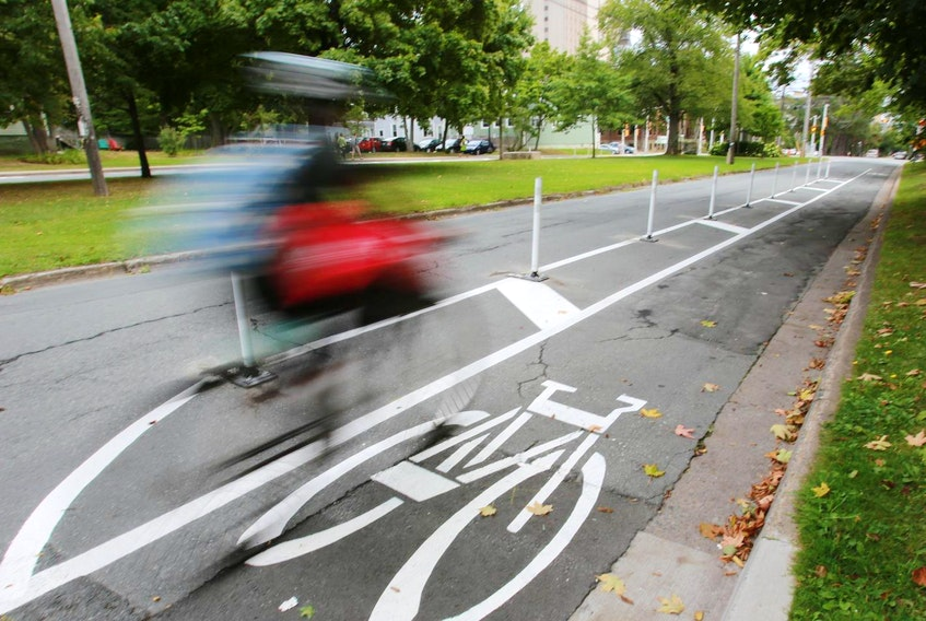 A cyclist whizzes by in a dedicated bike lane on University Avenue. - File