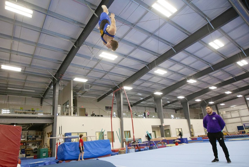 Trampoline athlete Kai Dwyer soars above the trampoline as coach Stewart Gunn watches. Dwyer will be competing in his second Canada Winter Games in Red Deer, Alta. - Eric Wynne