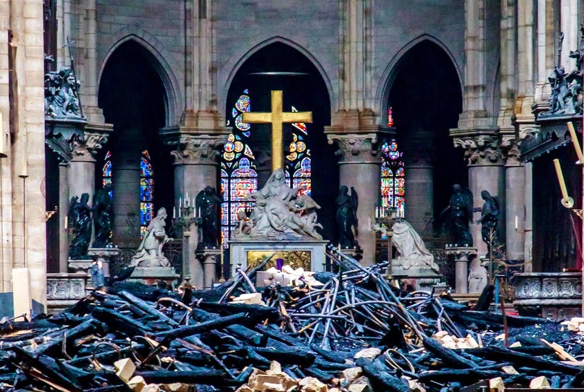 A view of the cross and sculpture of Pieta by Nicolas Coustou in the background of debris inside Notre-Dame de Paris, in the aftermath of a fire that devastated the cathedral. - Christophe Petit Tesson/Pool via REUTERS