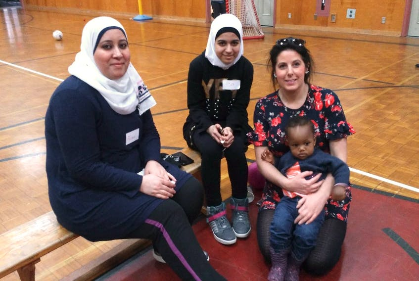 Rima Kenaan (left) and her daughter, Aya Kenaan (centre), a Grade 9 student at Digby Regional High School, are helping Lindsay Longmire (right) organize a cultural summit for students at the school on Tuesday, May 7. Elsa, sitting in Longmire's lap, is two years old and arrived here with her mom and three siblings in November from Ghana as refugees.
