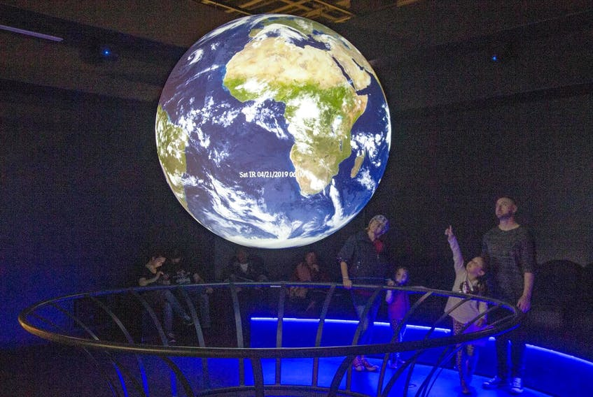 A family watches the world spin in the global projection display at the Nova Scotia Museum of Natural History in Halifax on Monday, Earth Day. - Tim Krochak