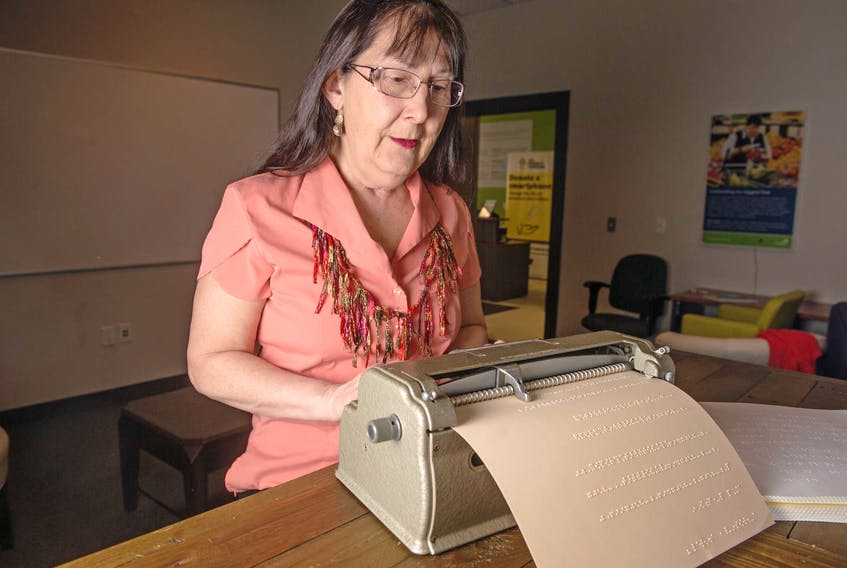 CNIB volunteer Genevieve Wales demonstrates how to use a Braille machine. - Ryan Taplin