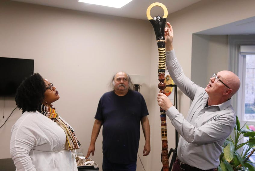 Wendie Poitras, left, and Alan Syliboy look on as fellow artist, Mark Austin, points out some of the symbolism on the New Dawn Staff. …… the three are some of the many artists who contributed to the design of the New Dawn Staff, seen at the Indigenous Student Centre at Dalhousie University on Tuesday May 14, 2019. The New Dawn Staff will replace the university's old convocation staff. - Tim Krochak