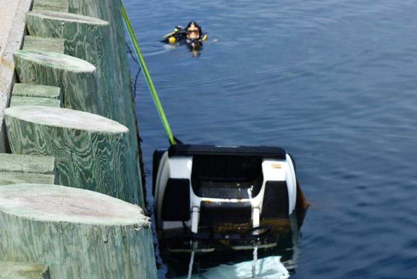A police diver helps recover a stolen golf cart near the government wharf in Canso. - RCMP photo