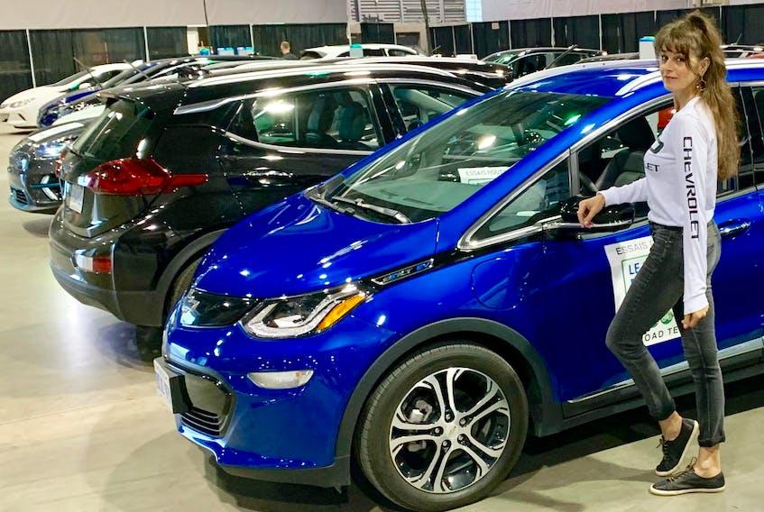 Lisa Calvi stands with the 2019 Chevrolet Bolt electric vehicle at Quebec City's Salon du véhicule électrique.