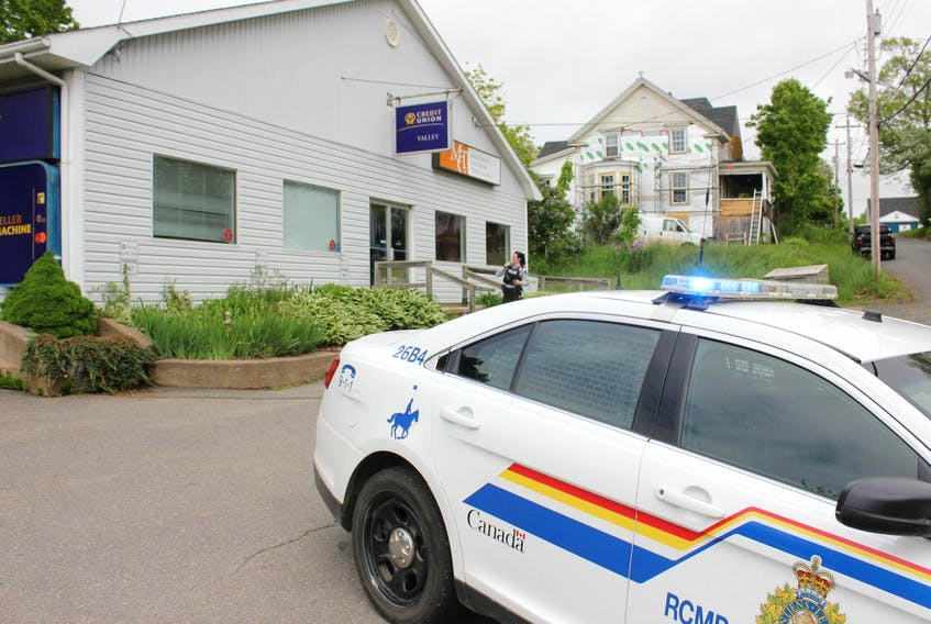An RCMP officer stands outside the Valley Credit Union branch in Canning Friday morning, after a shot was fired during an attempted armed robbery. - Ian Fairclough