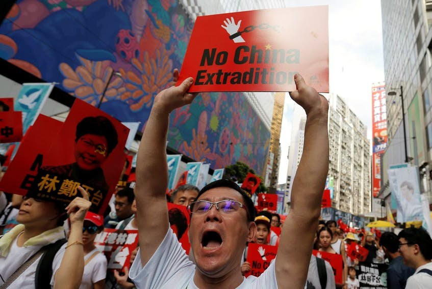 A demonstrator holds up a sign on June 9 during a protest in Hong Kong to demand that authorities scrap a proposed extradition bill with China. - Thomas Peter/Reuters