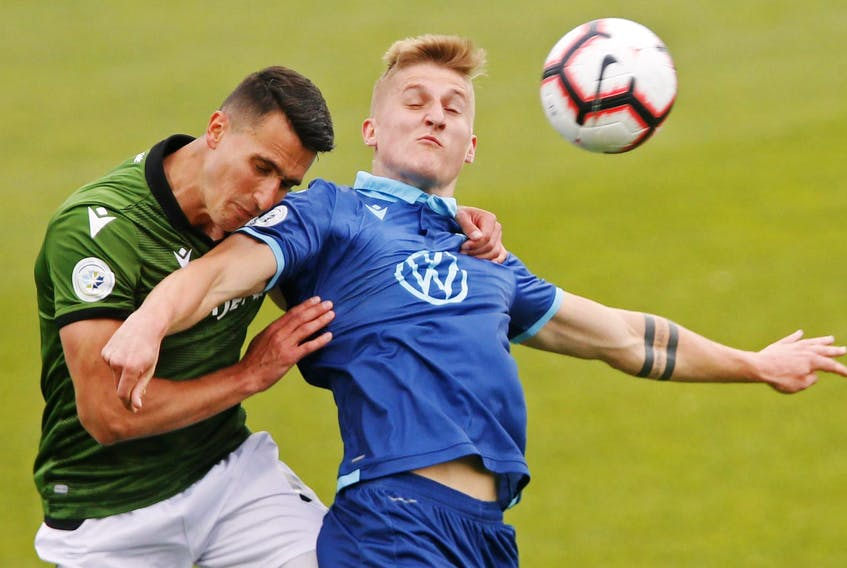 Cavalry FC's Dominick Zator, left and HFX Wanderers FC's Tomasz Skublak battle for a ball during CPL action at the Wanderers Grounds on Wednesday. - Tim Krochak