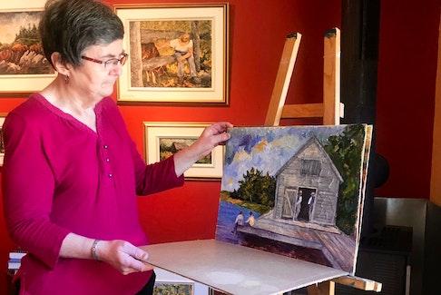 Acadian artist June Deveau looks through some works in progress in her studio behind her home in Saint-Alphonse. PAT LEE