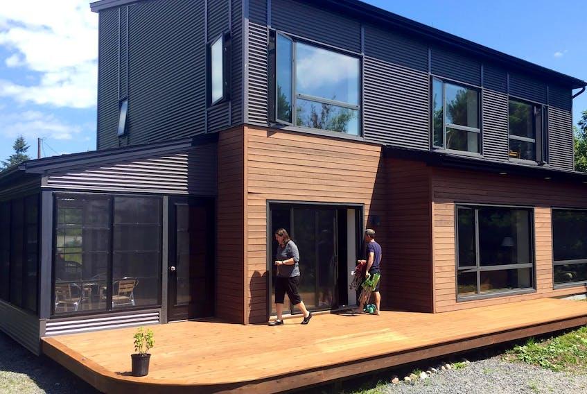 Designer of energy efficient homes, Natalie Leonard, owner of Passive Design Solutions, and homeowner Marcus Turner on the deck of Turner's lakefront house in Hubley.