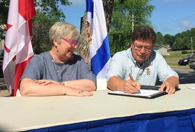 Federal Rural Economic Development Minister Bernadette Jordan watches as Nova Scotia Municipal Affairs and Housing Minister Chuck Porter signs a new provincial-federal community housing programs agreement. The agreement will see $394 million spent over 10 years building and repairing affordable housing in the province. - Ian Fairclough