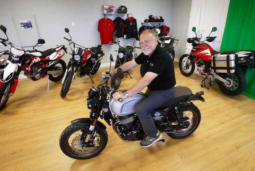 Bill Scott sits on one of the SWM motorcycles he sells at Moto Italia in Dartmouth. - Tim Krochak
