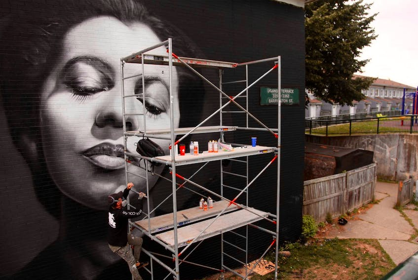 Artist JEKS climbs scaffolding as he works on his mural of the late Nova Scotian opera star Portia White, on a building unit at Mulgrave Park in Halifax on Aug. 26. JEKS was one of 14 muralists and artists contributing to Paint in the Park 2019.