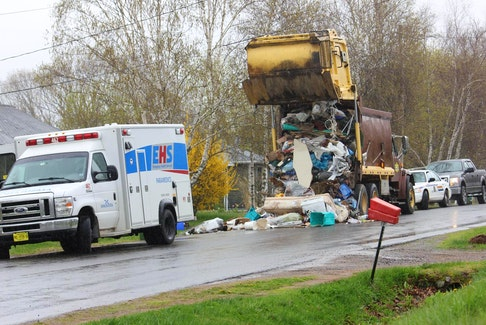 An RCMP officer and Labour Department investigator talk at the scene of a workplace accident involving a garbage truck in Port Williams on May 10, 2018. - Ian Fairclough