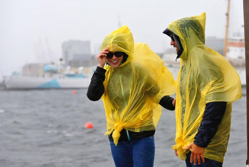 Laura Martin and Adrien Lacrois check out the wind and rain on the Halifax waterfront on Saturday afternoon before Dorian's arrival. - Tim Krochak