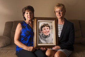 Sisters Elizabeth Deveau and Dorothy Dunnington hold a photo of their sister Chrissy who died last year from an infected bedsore. - Ryan Taplin