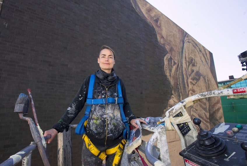 From her perch in a cherry picker above Hollis Street, artist Jacoba Niepoort poses for a photo in front of a mural she's creating in downtown Halifax on Thursday afternoon, Sept. 26, 2019. - Ryan Taplin
