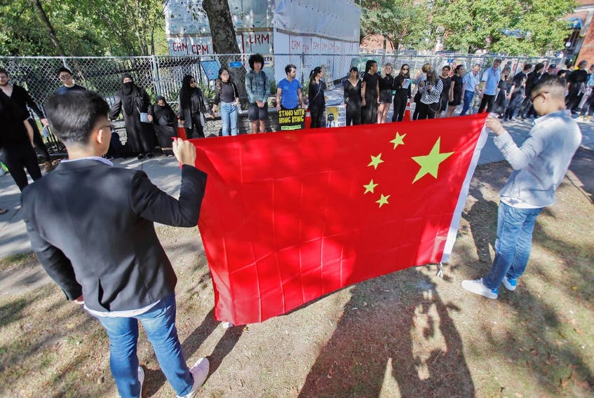 Protesters fighting for justice for the citizens of Hong Kong form a human chain along the fence that surrounds the Halifax Public Gardens on Saturday afternoon while those opposed to the protesters' views hold a Chinese flag in front of them.