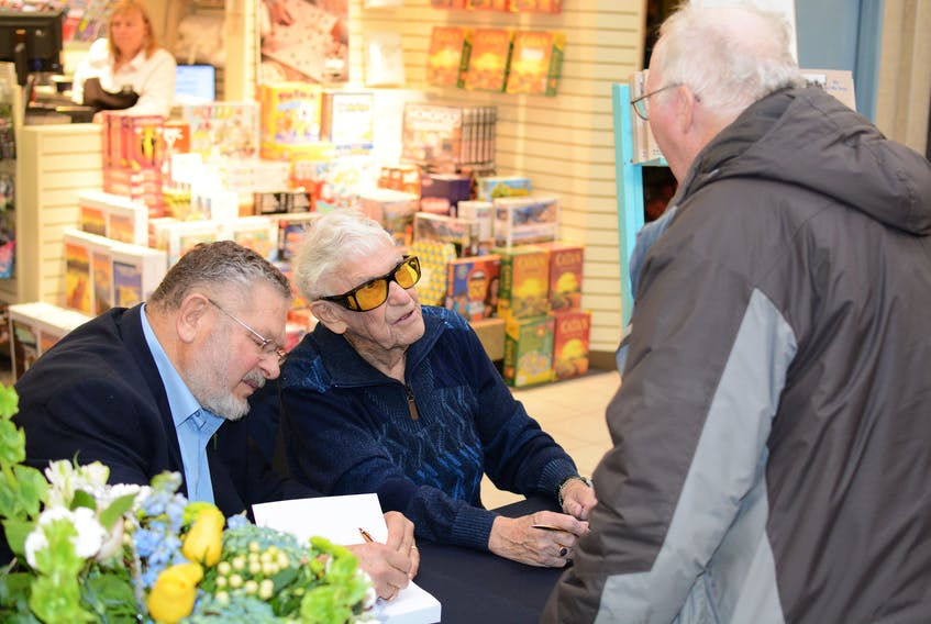 Roger Bacon talks with a friend, while Morris Haugg signs a book.