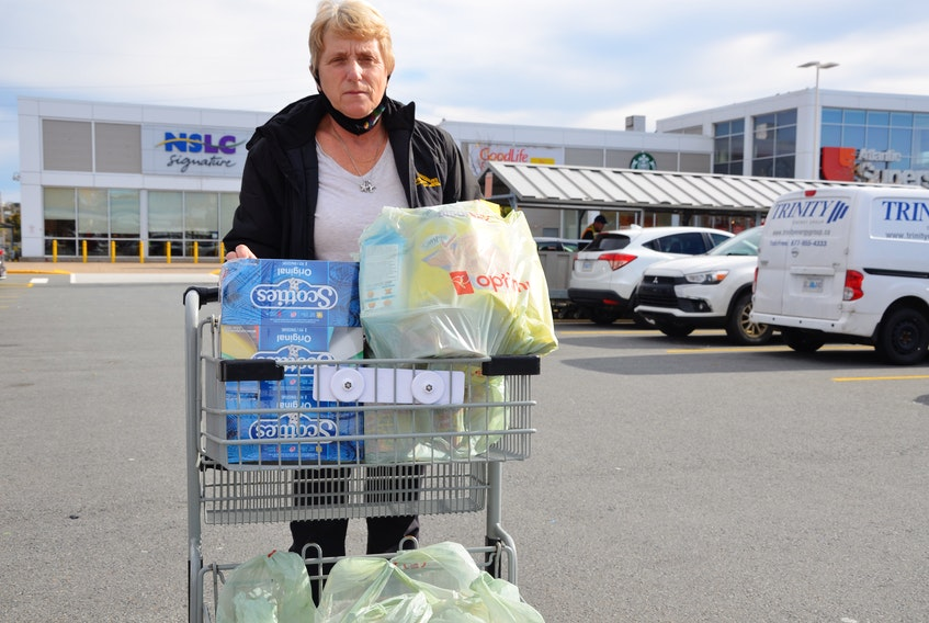 Bridgid Bowers wheels her grocery cart laden with plastic grocery bags across the parking lot of the Atlantic Superstore on Joseph Howe Drive in Halifax on Wednesday, Oct. 28. Bowers says the single-use plastic bag ban will not have much impact on her.