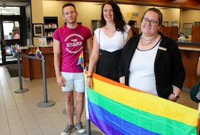 Pride Cape Breton communication director B.J. Singleton and Sydney Credit Union representatives Jennifer Griffin and Adrienne Collins, pose with the Pride flag inside their main branch, located on Townsend Street in Sydney. The bank is opening is helping Pride Cape Breton make the parade on August 3 more inclusive for people with sensory issues, anxiety and mobility issues. Inside will be the Autism Safe Zone, with dimmed lights and low sound.