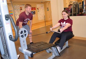 Julia Peck, right, 18, of Louisbourg, gets assistance on the seated cable row from her cousin Jamie Hunt, also from Louisbourg, at the YMCA of Cape Breton.
