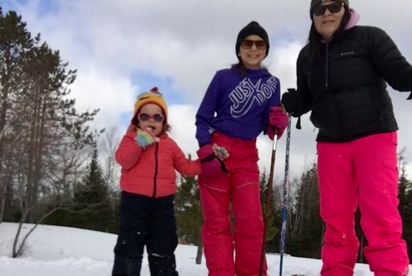 From left, Lucy Graves, her sister Lydia and her mother Marjorie enjoyed snowshoeing in the backyard of their Marion Bridge home last week, as part of their self-isolating activities while following COVID-19 precautions.