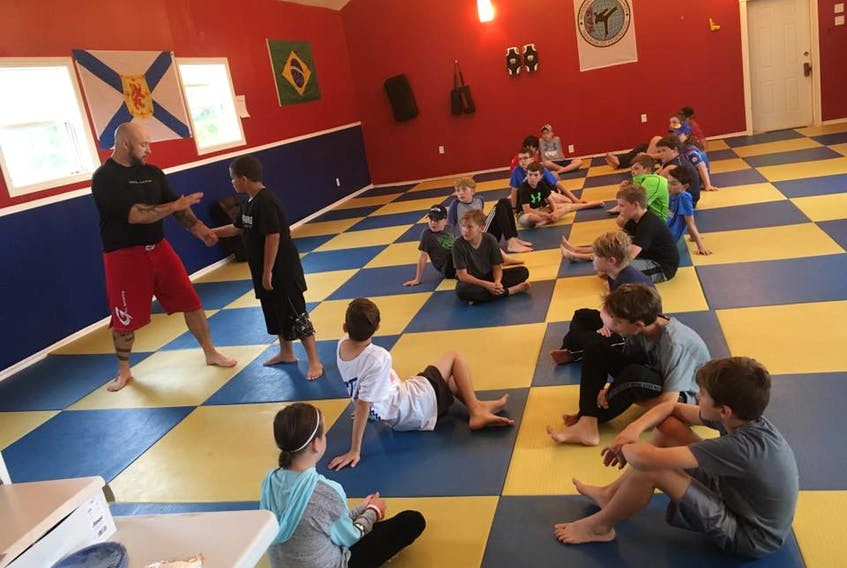 Jimmy Hall, owner of Integrity Martial Arts in Whitney Pier, teaches a group of kids how to get out of a wrist hold during an anti-bullying defence seminar in September.