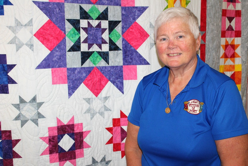 Jacquie Gillis, owner of the Mira Stitch 'n Post in Marion Bridge, is shown in her shop with one of the colourful quilts on display. Gillis has been in business at the location for 12 years and was recently named one of the top sellers of sewing machines in North America for SVP Worldwide.