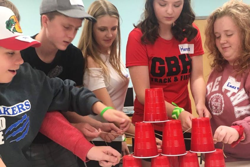 Hannah Livingston (fourth from the left), a member of the Glace Bay High School Headstrong group, works on a cup challenge with some former Oceanview Education Centre Grade 9 students entering Grade 10 Thursday (from the left) Jack Barry, Colton Deering, Nicole MacDonald and Emma Barrett. The challenge was part of an Amazing Race Glace Bay High Edition event to provide a fun way to introduce the students to the high school.