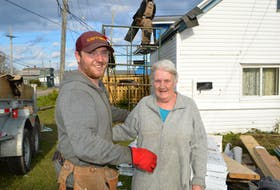 Jeremy Locke, owner of Locke's Roofing and Construction in Bridgeport, spends a few moments with Jeanette MacDonald of Glace Bay, while building her a new roof at his own expense, tired of seeing her and her grandchildren living with an old leaky roof. MacDonald said she's so grateful to Locke and other companies who have since stepped up to help in some way due to Locke's kind gesture.