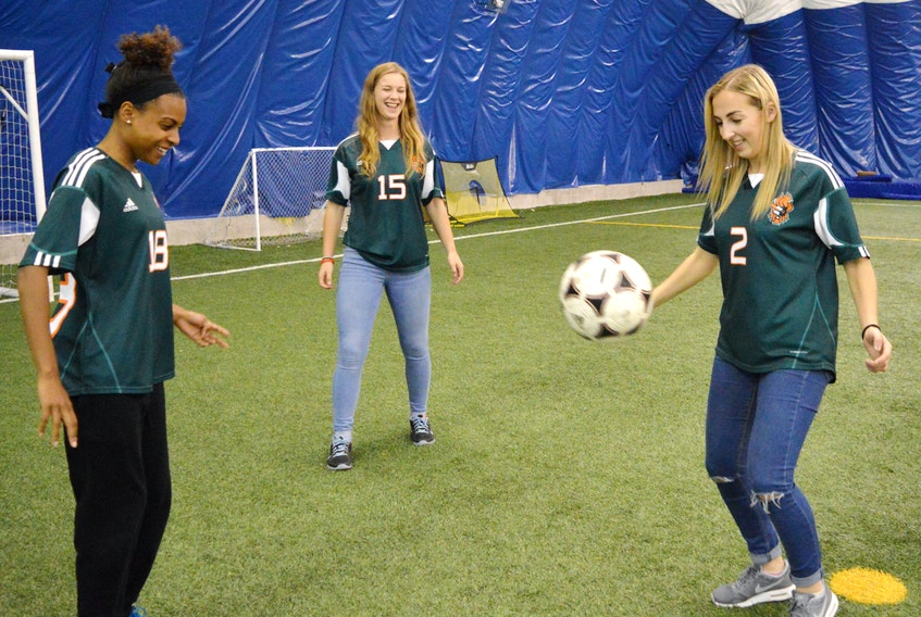 Tamara Brown, from left, Robyn Novorolsky and Alyssa Armstrong play around with a soccer ball at CBU on Monday. The team heads to the national soccer championships in Manitoba this week. CAPE BRETON POST PHOTO