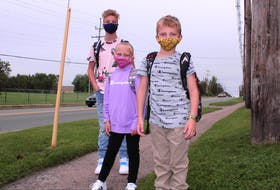 Siblings Bradley MacNeil-Burke, Ella Jessome and Brian Jessome are shown waiting for the school bus to take them to Coxheath Elementary and Riverview High on Tuesday, the first day of school for students in the Cape Breton Victoria Regional Centre of Education.