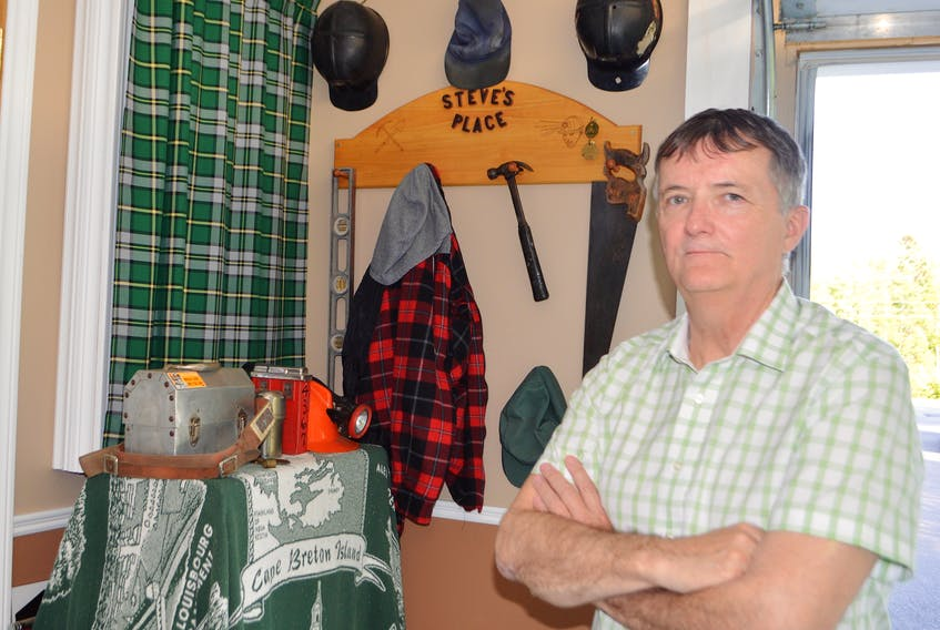 Steve Drake of New Waterford looks over a corner in his garage where he has a memorial to his coal miner father, the late Steve Drake Sr., that includes his father's favourite lumberjack shirt, work cap, hard hat and some tools, together with some of his own former coal mining equipment.