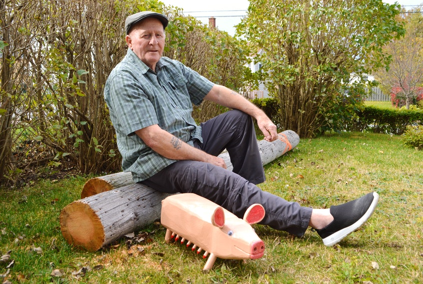 Cape Breton artist Murray Gallant sits on a utility pole in his yard on Heelan Street, New Waterford, with a pig he hand-carved from it. Gallant, 81, who has been hand-carving folk art for more than 40 years now, said he had been anxious to do some pieces and was wondering where he could get some wood when post-tropical storm Dorian hit and left a telephone pole hanging by its wires at his front gate. Gallant has 16 pieces of his folk art preserved in the Art Gallery of Nova Scotia.