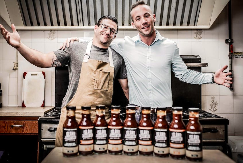 Island Sauce Company business partners Nathan Susin, left, and Keven Taylor, pose with jars of their sauce at the Polish Village Hall in Whitney Pier.