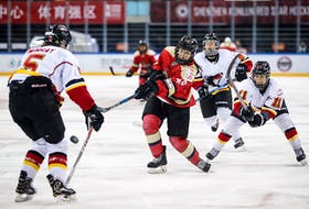 Baddeck's Jessica Wong, middle, fires the puck in a game against the Calgary Inferno during the 2017-18 season. Wong came out of retirement to play for the Kunlun Red Star, one of two expansion teams from China in the Canadian Women's Hockey League.